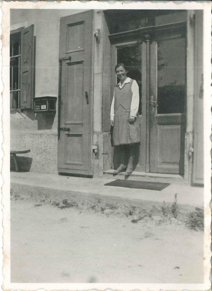 Na fotografiji:poštna upravnica Ivanka Bizjan pred poštnim uradom v Polhovem Gradcu ok. leta 1930, hrani družina Bizjan